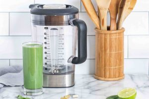 blended green smoothie in the white kitchen with wooden spoon on the side