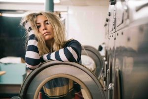 stressed mother feeling tired doing the laundry in the open door of washing machine