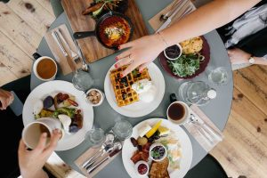 table of yummy food choices in a wooden table outside the house with girl hand reaching for waffles